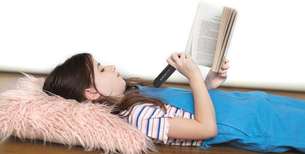Young Girls using OrCam Device to read a book while laying on the floor
