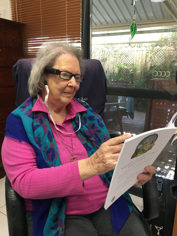 Sybil using her OrCam MyEye to read a book