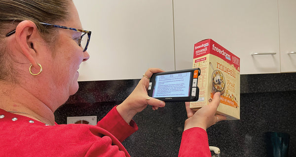 Tara using her Clover 6 device to magnify food label text