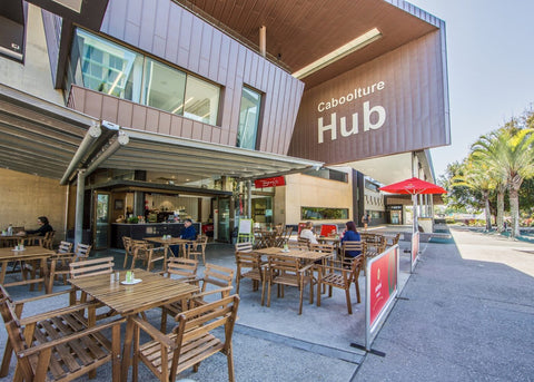 Outside shot of Caboolture Business Hub, with tables, chairs and cafe in the foreground