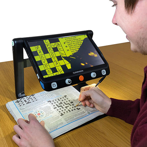 Man doing crossword puzzle using Clover Book Lite to magnify the page