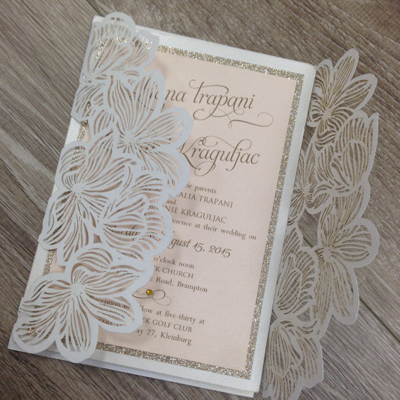 white laser cut wedding invitation with blush pink and