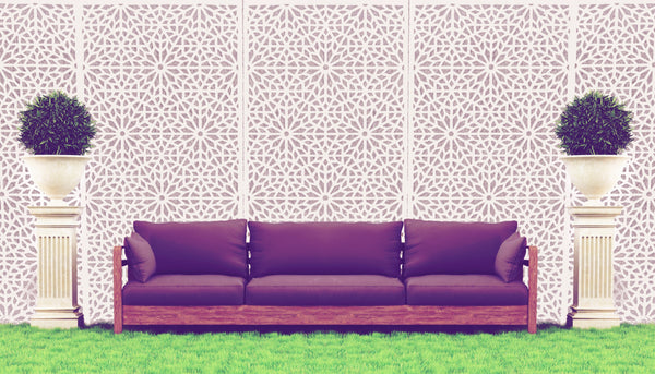 Cream designer geometric pattern screen installed behind a sofa in a garden