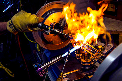 Photo of lampworker at Mothership Glass constructing a complex pipe on a glassblowing lathe.