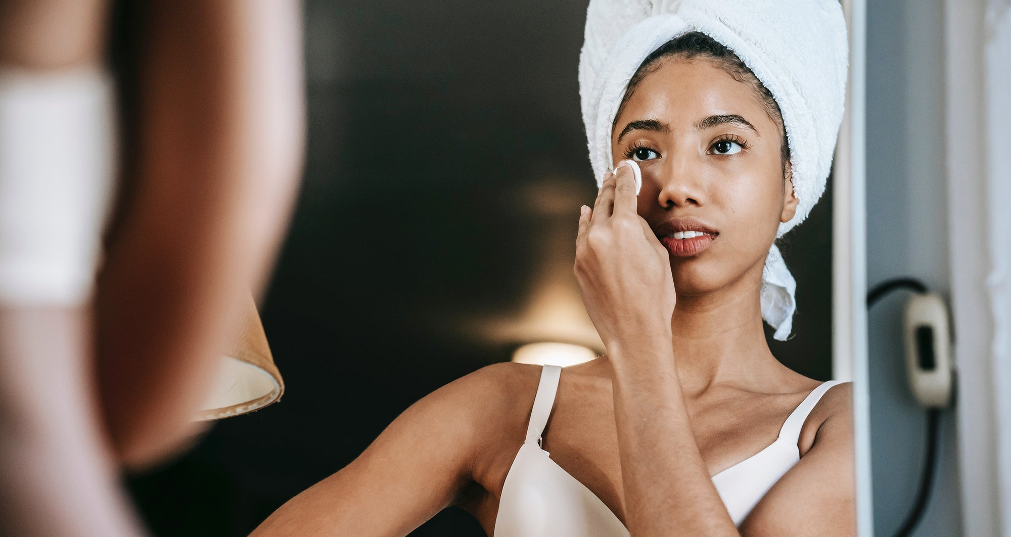 Beautiful Young working woman getting ready in the morning in front of her mirror, applying her skincare routine.
