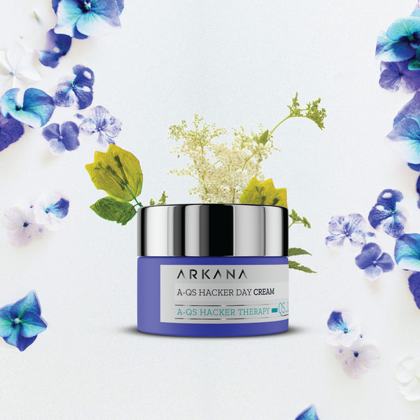 Navy blue bottle for A-QS Hacker Day Cream with blue flowers flourishing in the background. Arkana Canada Neuro Cosmetics. Light mattifying day cream targeting oily, combination, acne-prone skin.