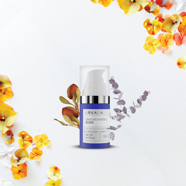 Navy blue bottle for UniTone Forte C Elixir with small pump in front of orange, yellow, and purple floras. Part of UniTone Neuro Therapy by Arkana Canada Neurocosmetics. Used to prevent and fight against discolouration and uneven tones.