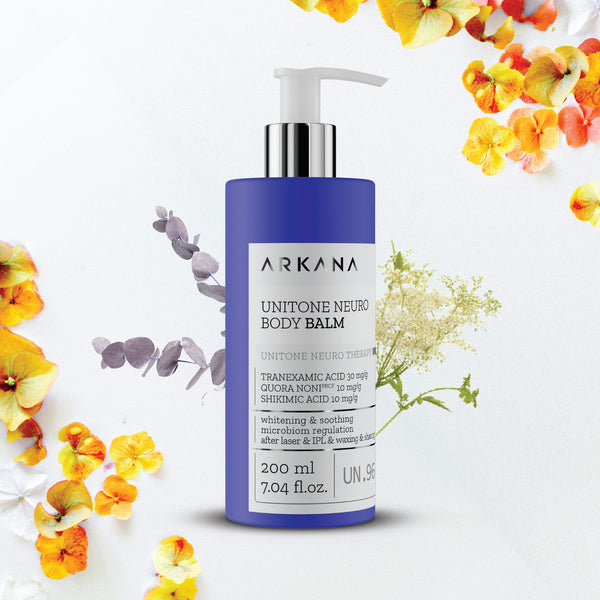 Navy blue bottle for UniTone Neuro Body Balm in front of purple and white florals. Part of UniTone Neuro Therapy by Arkana Neurocosmetics. Brightening balm recommended for face and/or body care after hair removal.
