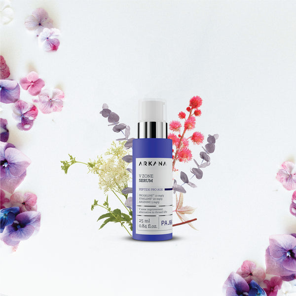 Navy blue bottle for V Zone Serum by Arkana Neuro Cosmetics. Bottle is placed in front of pink, lilac, green, white florals. Part of Peptide Pro Age Therapy Line which focuses on powerful anti-aging effects. This Serum is used for for face contouring and powerful skin lifting to shape oval face.