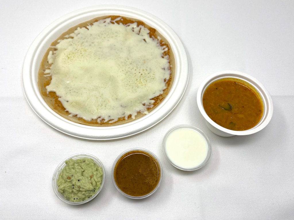 Rice and lentil pancake with cheese served with sweet yogurt, coconut chutney, tomato/mint chutney, and sambhar