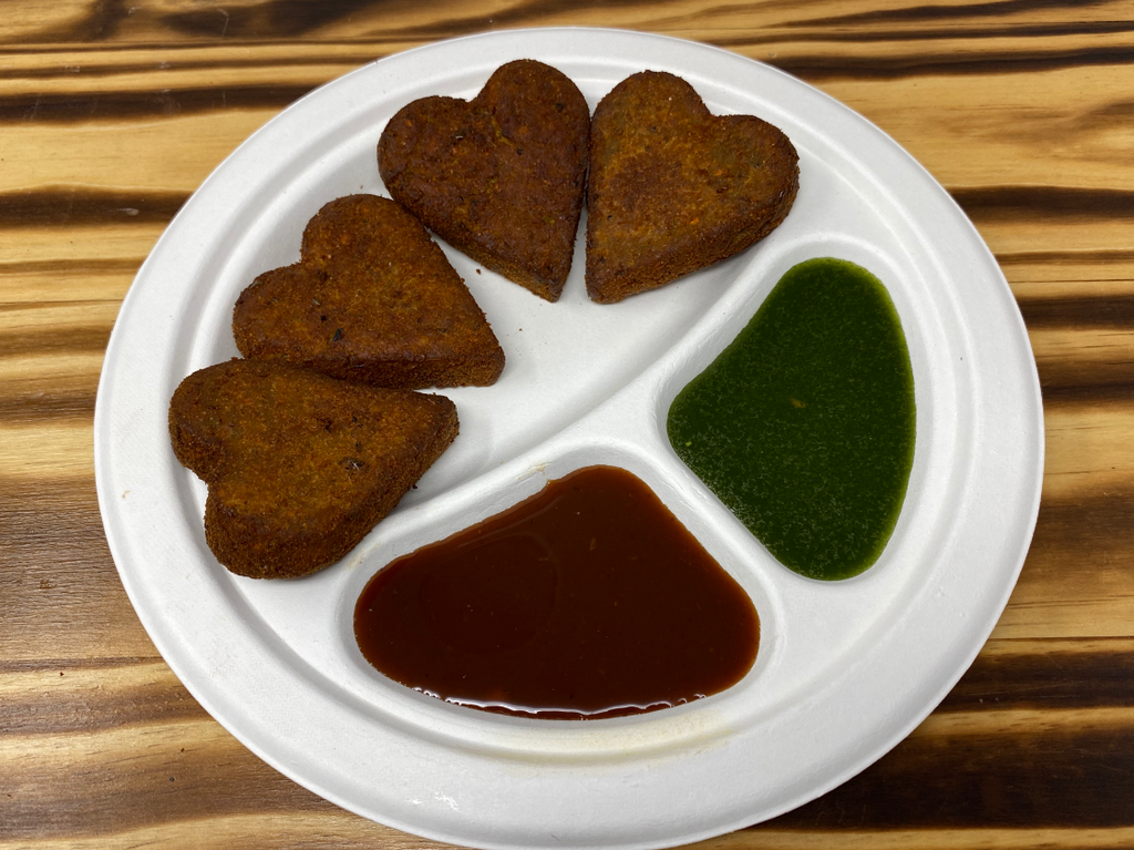 Deep-fried mixed vegetable patties served with sweet chutney and hot chutney
