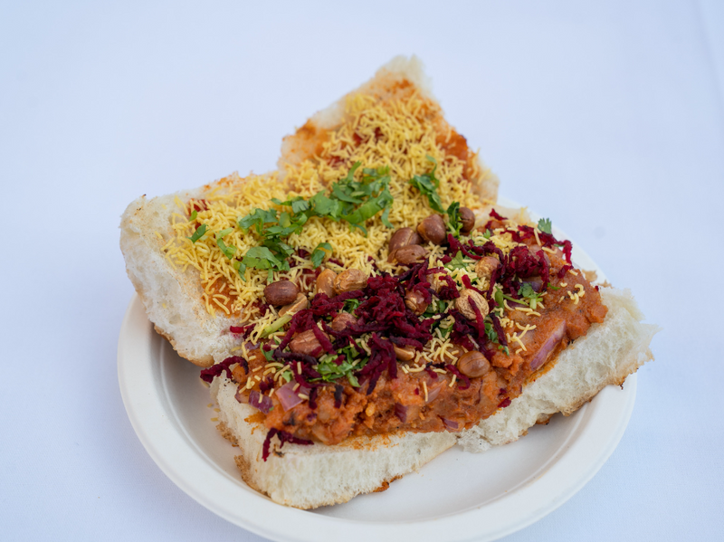 Spicy and tangy potato filling stuffed in a bun with peanuts, onions, dabeli chutney, and thin chickpea flour noodles (Sev)