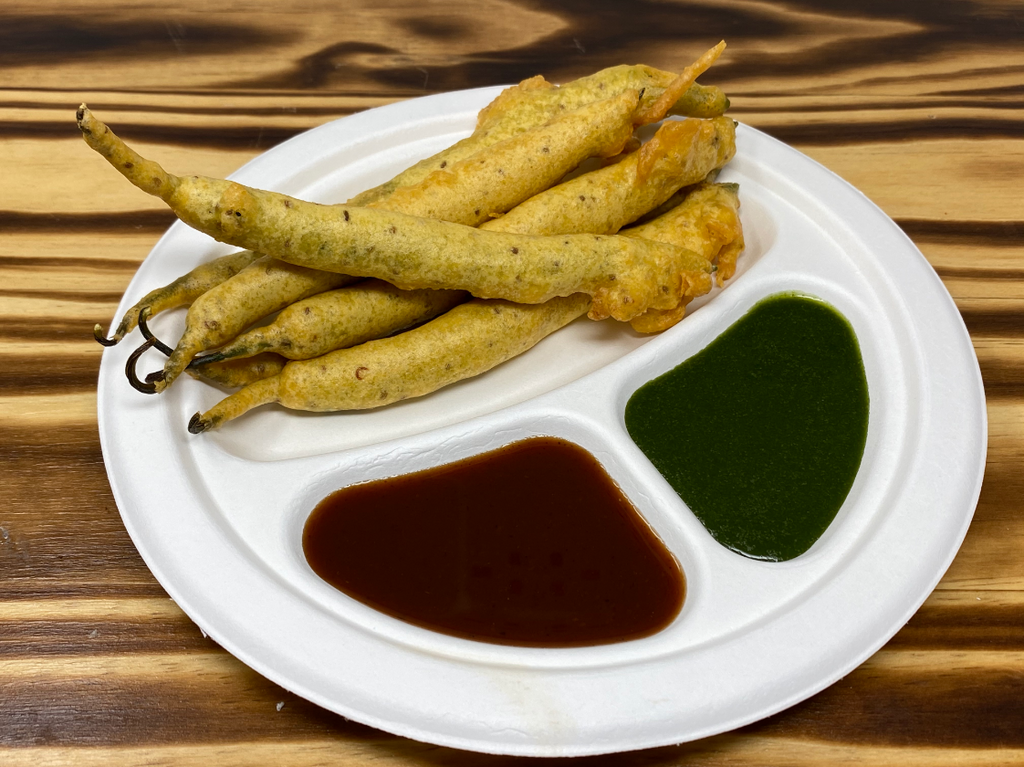 Deep-fried seasoned peppers coated with chickpea flour served with sweet chutney and hot chutney