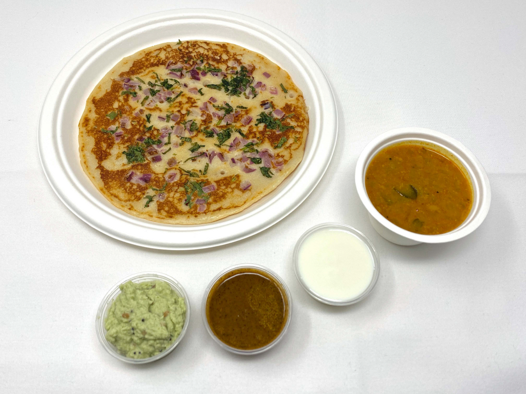 Rice and lentil pancake with onions and green peppers served with sweet yogurt, coconut chutney, tomato/mint chutney, and sambhar