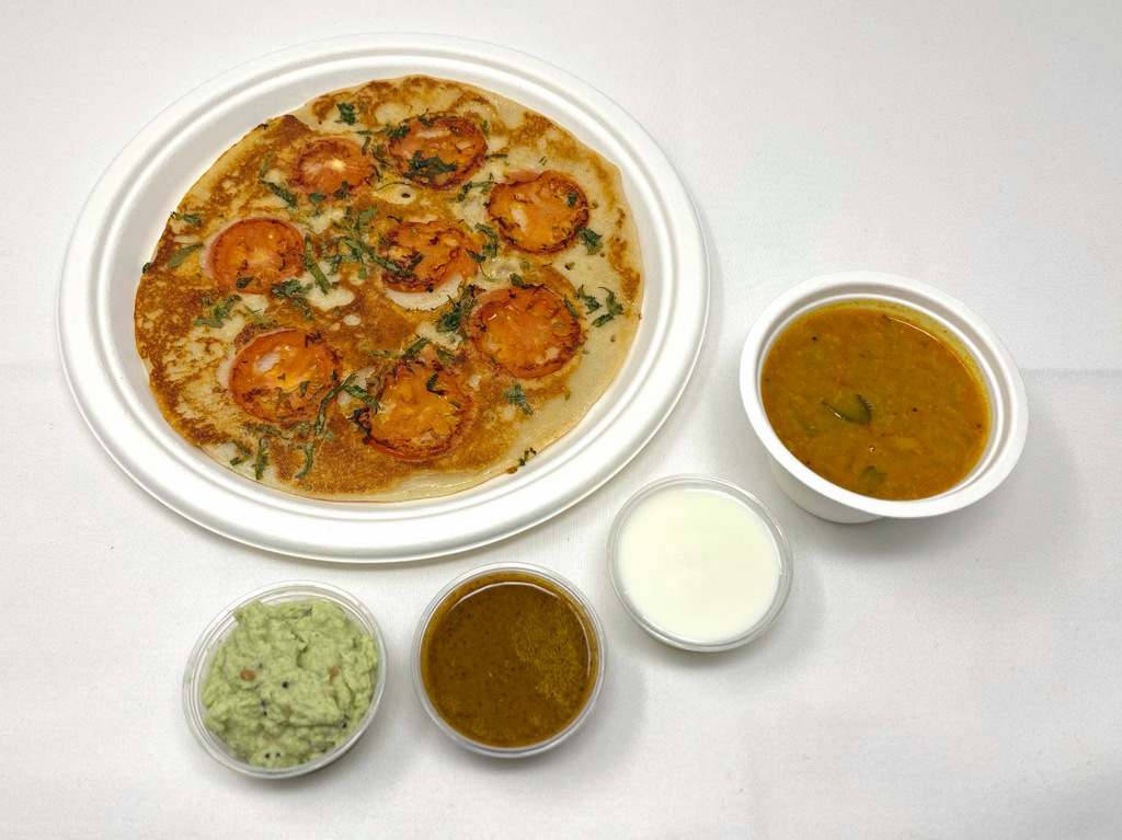 Rice and lentil pancake with tomatoes served with sweet yogurt, coconut chutney, tomato/mint chutney, and sambhar