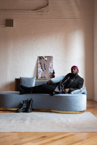 Quentarius Higgins sitting on Infinity gray velvet couch
