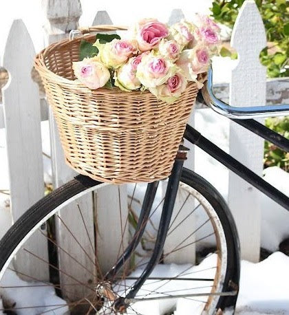 Bicycle with a front basket filled with roses