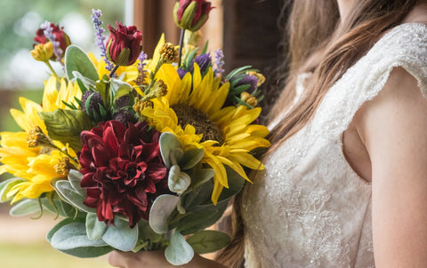 bride holding a beautiful bouquet of sunflowers