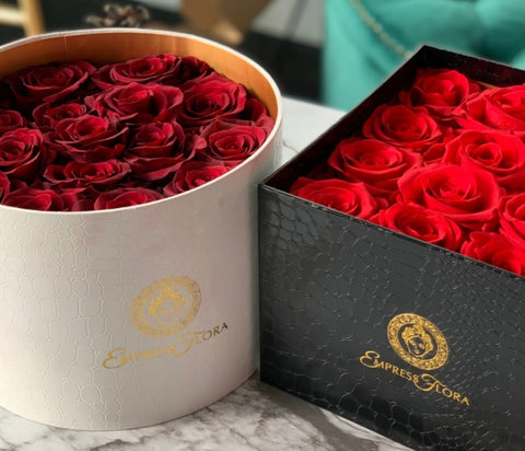 picture of white circle container and a black box containing a bouquet of preserved red roses