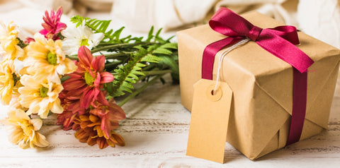 present box with brown tag and flower in bunch table