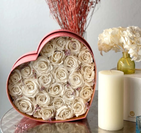 preserved white roses in a heart shape pink container
