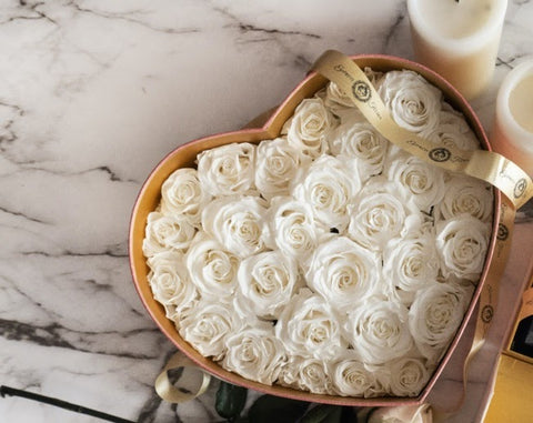 set of preserved white roses in a heart shape container