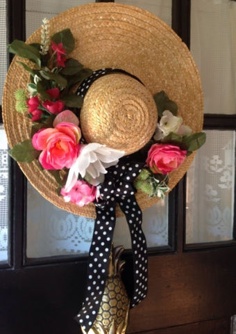 sun hat hang in the wall decorated with flowers