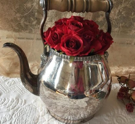 teapot filled with red roses