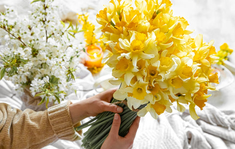 woman holding bouquet yellow daffodils