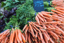 Load image into Gallery viewer, Fresh carrots at a market