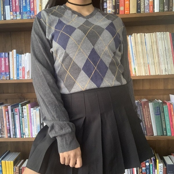 Green argyle sweatshirt paired with a black pleated skirt