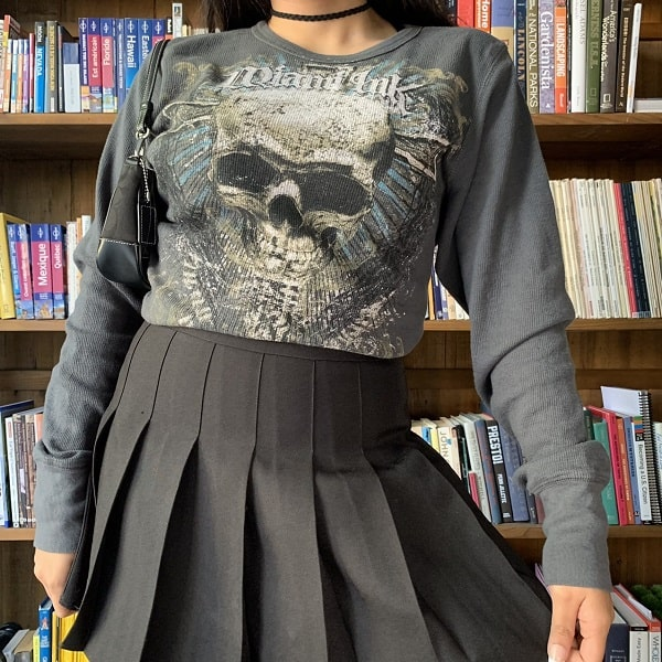 Vintage skull graphic tee paired with a black pleated skirt