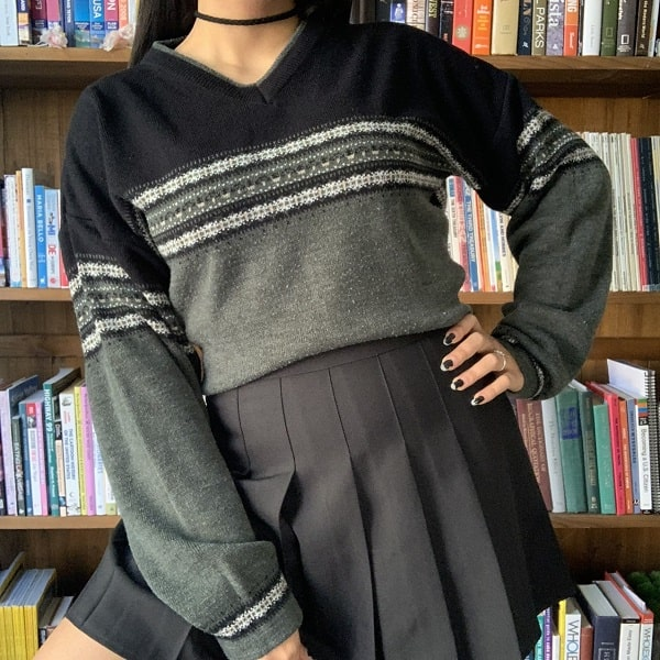 Green 90s striped sweatshirt paired with a black pleated skirt
