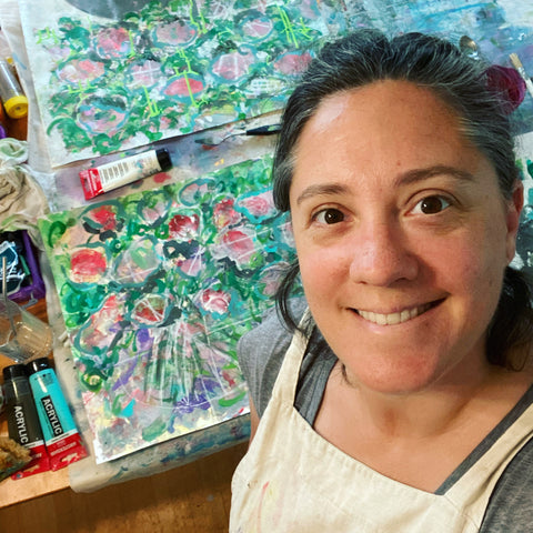 artist smiling up at camera with apron covered in paint. colourful floral painting in progress in background