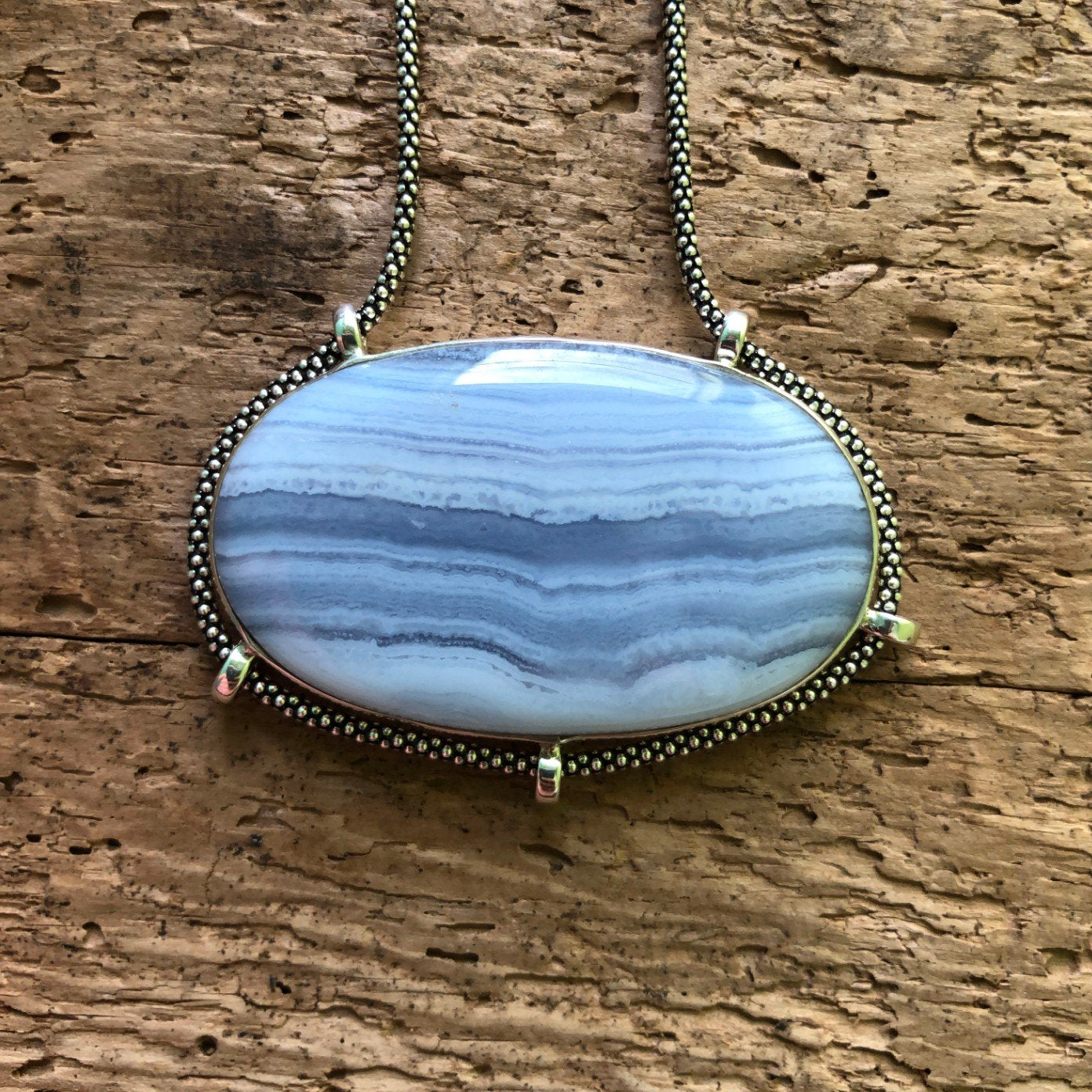 Strikingly good quality horizontally oriented oval Blue Lace Agate Pendant with oxidized sterling silver chain on driftwood background