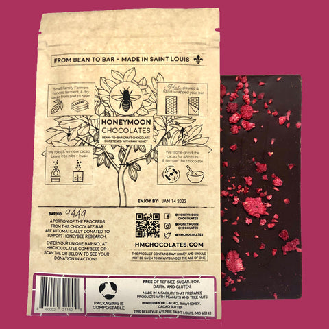 A photo of Honeymoon Chocolate's 70% Peruvian Dark Raspberry bar, the back of the bar is facing the camera so the raspberries are exposed and it is next to the packaging