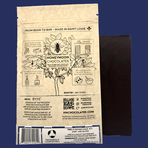 A photo of our 85% Haiti Dark Chocolate Bar next to the back of its packaging which is a pale cream and dark indigo color