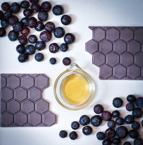 A honeymoon Chocolates bar is sitting next to a cup of honey and blueberries