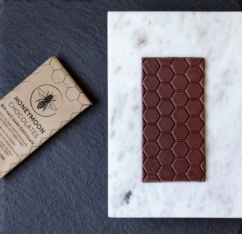 A photo of Honeymoon Chocolate's Haiti Chocolate bar on a slab of marble with is wrapper next to it