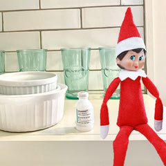 Elf on the shelf posing with 4 Vial Safe insulin protectors in dark green red white and gold holiday décor background