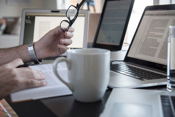man working with three screens and coffee