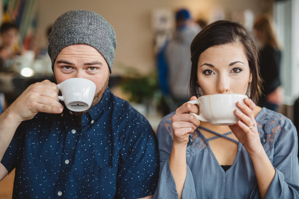 Young couple drinks coffee together while sitting an a coffee shop.