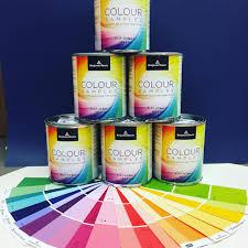 6 colour sample paint cans stacked in a pyramid formation with rainbow of colour sample cards below it