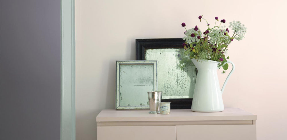 small table against wall with picture frames and vase with flowers