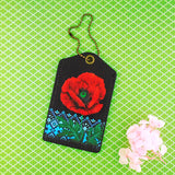 Shop Mlavi Studio's vegan leather luggage tag for women with Ukrainian poppy flower & embroidery pattern print. Great for everyday use & a unique gift for yourself & family & friends. More Ukraine themed bags, wallets & other fashion accessories are available for wholesale at www.mlavi.com for gift shop & boutique buyers worldwide.
