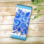 Shop Mlavi's vegan leather large flat wallet for women with blue and white Ukrainian Petrykivka style flower print. Great for everyday use & a unique gift for yourself & family & friends. More Ukraine themed fashion accessories available for wholesale at www.mlavi.com for gift shop & boutique buyers worldwide.