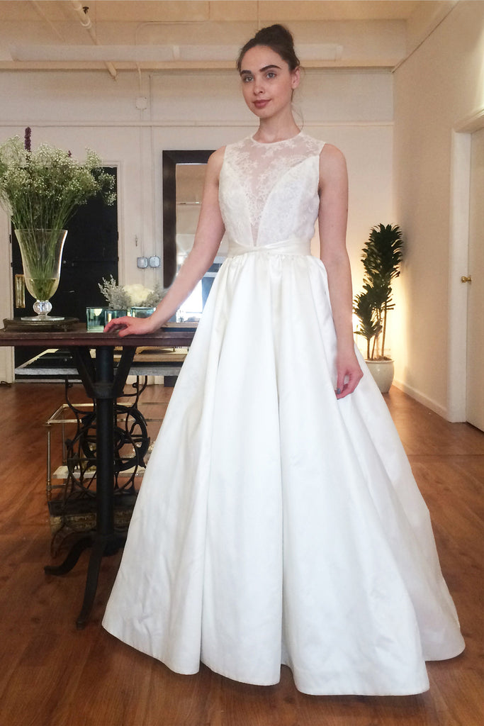 Lace sleeveless illusion bodice with deep V front. Duchess Taffeta twisted belt at waist and ballgown skirt.