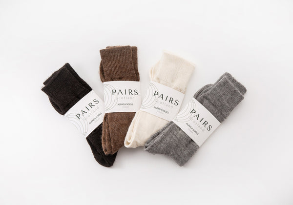 sustainable natural undyed alpaca wool socks product collection, four pairs piled up