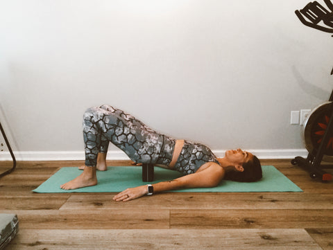 Laying on your back with a yoga block on the tailbone to lengthen the lower back muscles