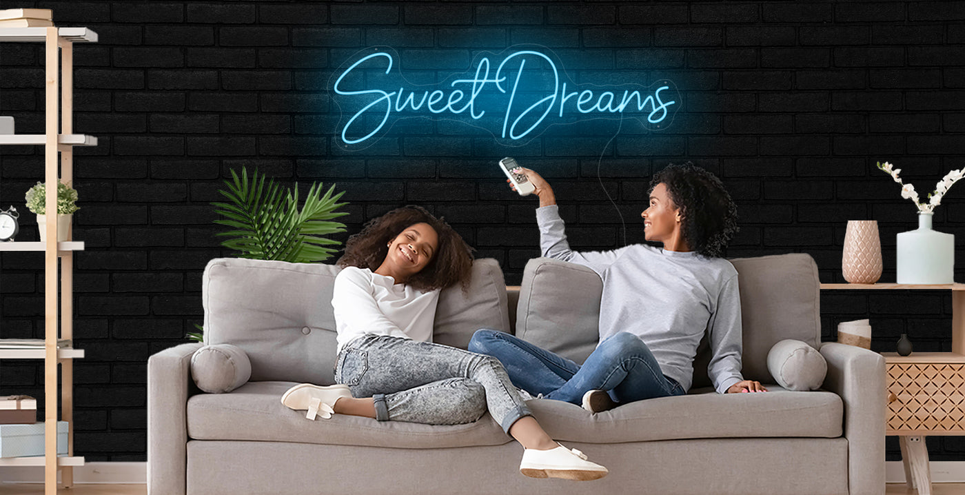 mother and daughter sitting on tan couch in living room using a remote control to turn on a light blue Sweet Dreams LED neon sign hanging on the wall